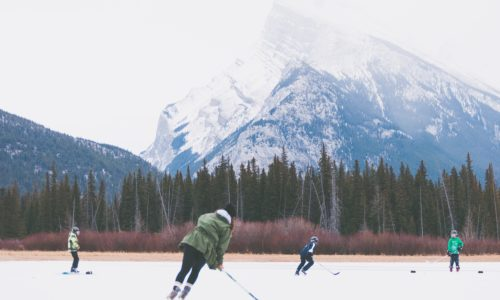 People playing hockey on frozen lake surrounded by forest overlooking snowy mountains