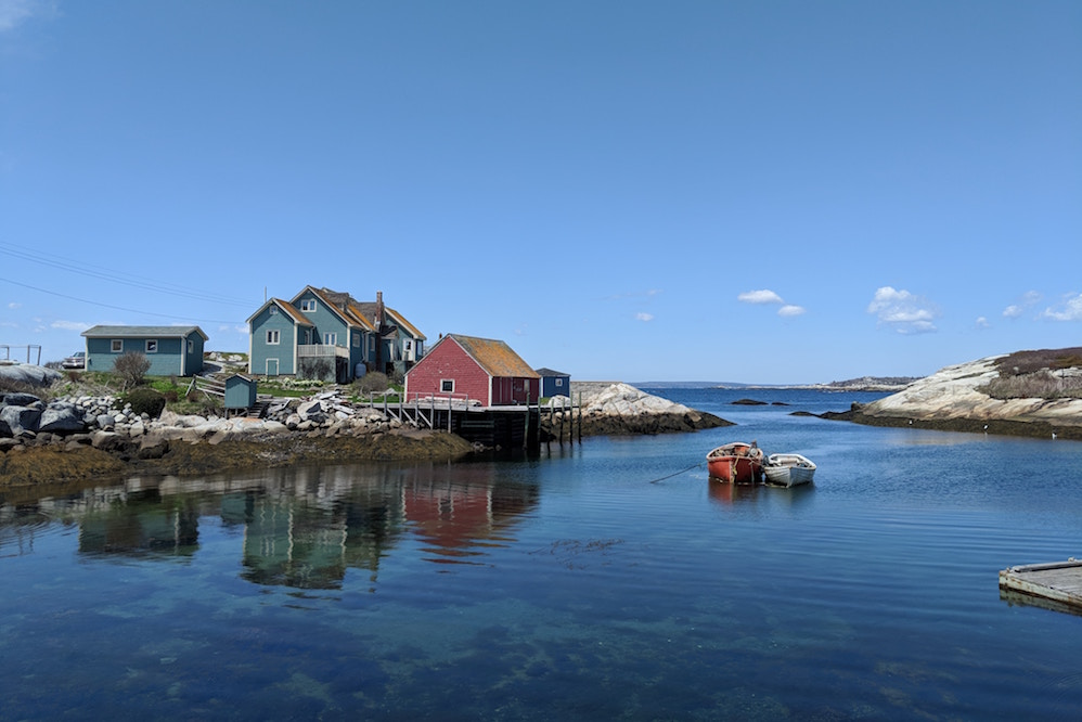 Colourful east coast houses stand over a harbour