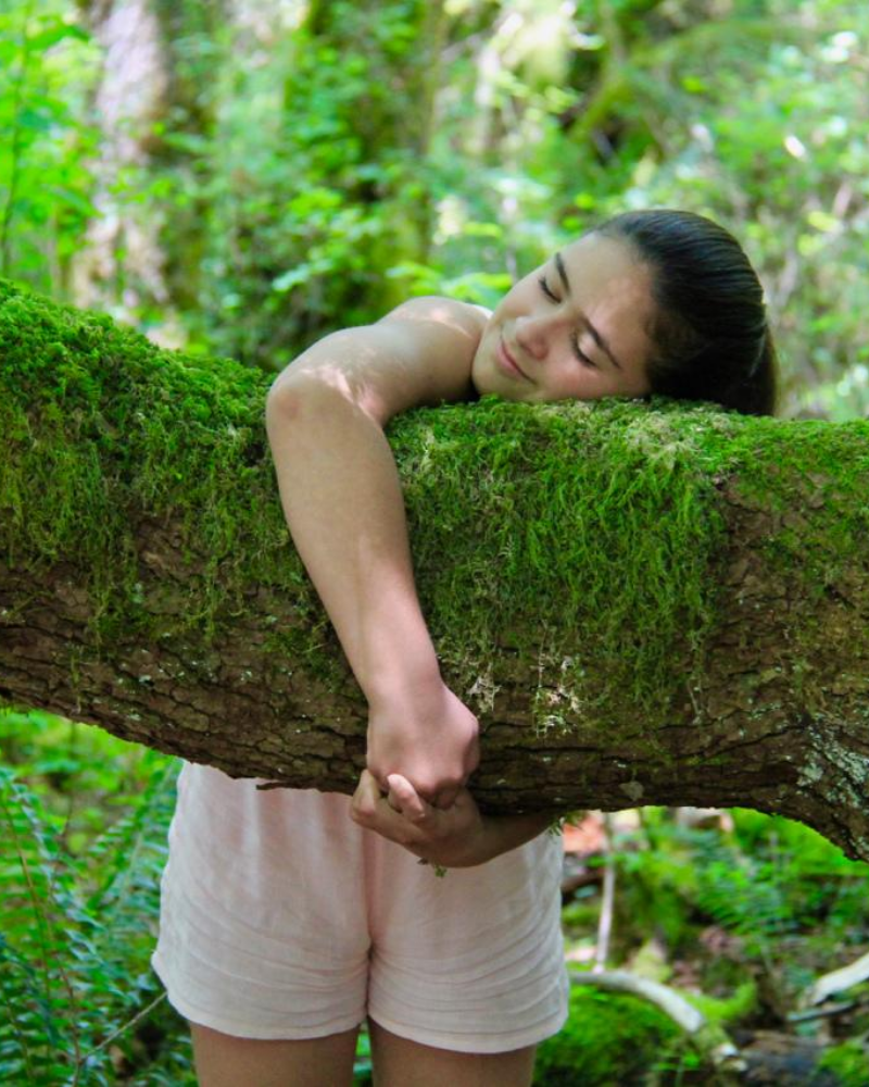 Young girl hugging tree