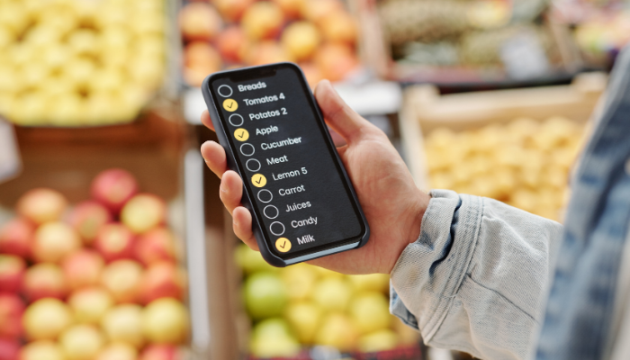 Person holding phone with grocery shopping list in front of produce