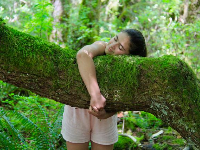 Young girl hugging tree