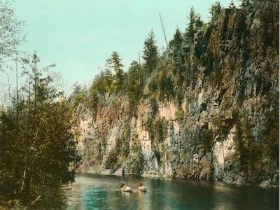 Vintage photograph of people canoeing in Algonquin Park surrounded by trees