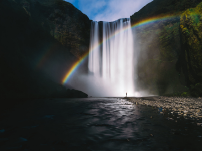 Person standing below waterfall with rainbow